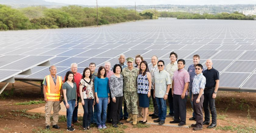 members of the Hawaii government, energy utility and military smiling in front of a large array of solar panels