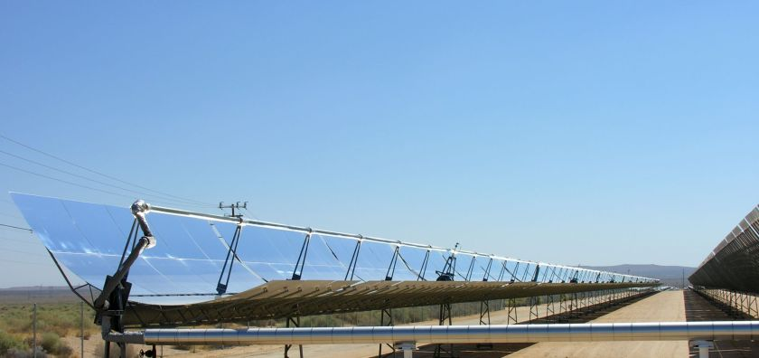 Solar trough reflecting a blue sky with desert in the background