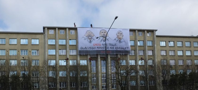 greenpeace action against smog - activists climb a building to hang a banner that says in polish that politicans are ignoring smog)