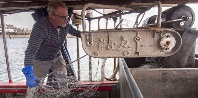 Fisherman Barratt holds an empty net inside of his boat