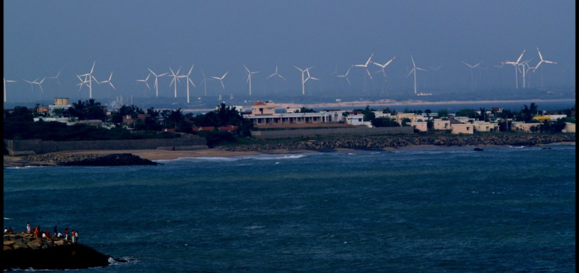 windmills seen from the coastline with people looking from an island