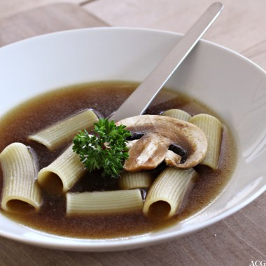 Tallerken med klar soppsuppe med pasta