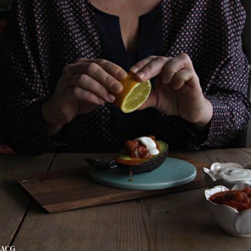 Bilde av ei som skviser sitronsaft over en halv avokado med salsa og rømme