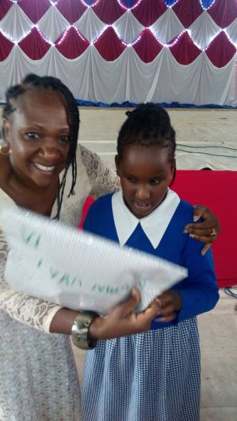 A student from Kilimani Primary School receiving a reward.