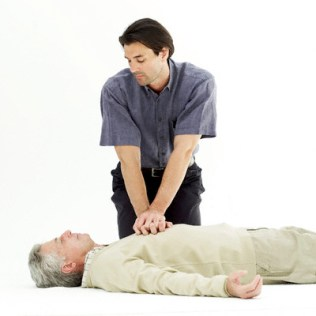 Young Man Doing Chest Compressions on Elderly Man