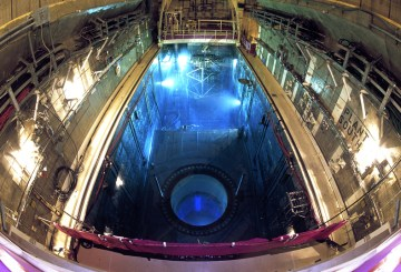Inside the reactor a fuel bundle glows with a vibrant blue light known as Cerenkov radiation, produced as escaping neutrons are slowed by water.