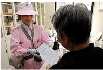 An electric meter inspector handing a leaflet to a customer