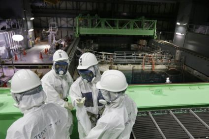 Workers stand in front of the Unit 4 Spent Fuel Pool