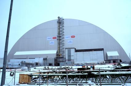 A view of the New Confinement Structure from the west. The western end of the turbine building can be seen on the lower right half of the New Confinement Structure.