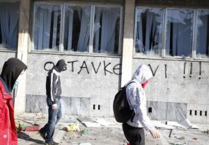 Protesters walk in front of a damaged government building in Tuzla February 7, 2014. REUTERS/Dado Ruvic (Bosnia and Herzegovina - Tags: politics, civil, unrest)