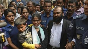 Two owners of Tazreen Fashions, Delwar Hossain, center left, and his wife, Mahmuda Akter, right, are escorted by security personnel to a court in Dhaka, Bangladesh, on Sunday, February 9, 2014. (AP Photo)