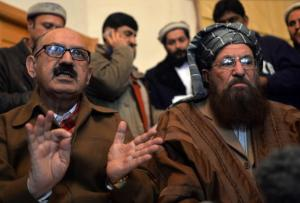 Maulana Sami-ul-Haq, a senior figure from the Pakistani Taliban looks on as Special Assistant to Pakistan's prime minister Irfan Siddiqui, left, speaks during a joint press conference following their meeting in Islamabad, Pakistan, on February 6, 2014. (AFP Photo/Aamir Qureshi)