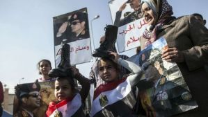 Supporters of Egypt's army chief Field Marshal Abdel Fattah al-Sisi, who is to run for the presidency in the upcoming elections, hold military boots on their heads in a sign of support for military rule, while wearing their national flag as others hold posters bearing the image of the military commander (bottom R and L) and late Egyptian president Anwar Sadat (top) during a demonstration outside the Police Academy in Cairo where a new hearing in the trial of deposed president Mohamed Morsi opened on January 28, 2014. Morsi went on trial on charges of breaking out of prison during the 2011 uprising against veteran strongman Hosni Mubarak. AFP PHOTO / MAHMUD KHALED