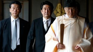 Japan's Prime Minister Shinzo Abe (C) is led by a Shinto priest as he visits Yasukuni shrine in Tokyo in this December 26, 2013, file photo. (REUTERS/Toru Hanai/Files)