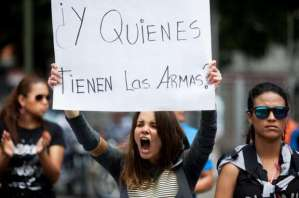 """A student from the Alejandro Humboldt University holds up a sign that reads in Spanish """"And who has the weapons?"""" as she shouts slogans against Venezuela's President Nicolas Maduro to protest yesterday's killing of Bassil Da Costa, at the Alejandro Humboldt University where he studied in Caracas, Venezuela, Thursday, Feb. 13, 2014."""
