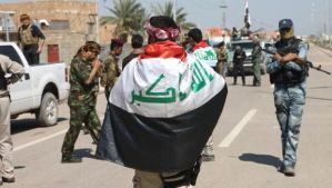Wrapped in the Iraqi flag, police and security gather along Street 60 after the southern districts of the city of Ramadi, the capital of the Anbar province, were recaptured by government forces from militants, on March 16, 2014. (AFP Photo/Azhar Shallal)