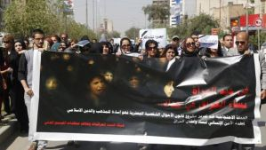 Iraqi protesters hold a banner during a demonstration against the draft of the Ja'afari Personal Status Law during International Women's Day in Baghdad on March 8, 2014. (Reuters/Thaier Al-Sudani)
