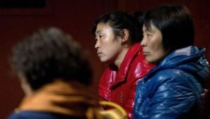 Chinese relatives of passengers aboard a missing Malaysia Airlines plane wait inside a hotel room in Beijing on Monday, March 10, 2014. (AP Photo/Andy Wong)
