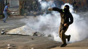An opposition activist returns tear gas to riot police during a protest against the government of Venezuelan President Nicolas Maduro in Caracas on March 5, 2014. (AFP Photo/Juan Barreto)