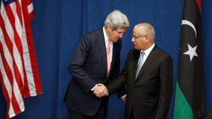 US Secretary of State John Kerry shakes hands with Libyan Prime Minister Ali Zeidan at the Conference on International Support to Libya, on March 6, 2014, in Rome. (AP Photo/Kevin Lamarque, Pool)