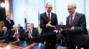 Ukrainian Prime Minister Arseniy Yatsenyuk (2-R) and EU Council President Herman Van Rompuy (R) exchange documents during the signing ceremony of political provisions of the Association Agreement with Ukraine at EU council headquaters in Brussels, Belgium, on March 21, 2014. Applauding are British Prime Minister David Cameron (3-L), Swedish Prime Minister Frederik Reinfeldt (2-L) and Finnish Prime Minister Jyrki Katainen (L). (EPA/OLIVIER HOSLET)