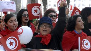 Tunisian women hold national flags as they take part in a march marking International Women's Day on March 8, 2014, in the capital, Tunis. (AFP PHOTO/FETHI BELAID)