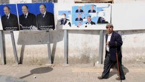 A man walks past electoral posters for incumbent President Abdelazis Bouteflika (L), and candidate Ali Benflis on Tuesday, April 15, 2014, in Algiers. (AP Photo/Ouahab Hebbat)