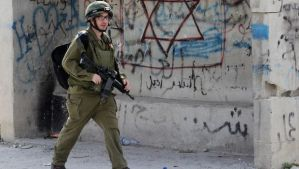 A member of the Israeli security forces walks past a shelter covered in graiffitti including Arabic text and the Star of David as they conduct house searches in the West Bank village of Der Samet on April 24, 2014. (AFP PHOTO/HAZEM BADER)