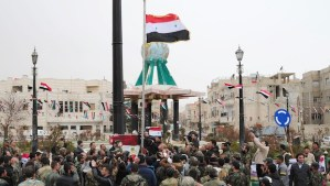 A handout picture released by the official Syrian Arab News Agency (SANA) on March 17, 2014, shows Syrian pro-government forces and supporters of Syrian President Bashar Al-Assad hoisting their national flag in the western town of Yabrud. (AFP PHOTO/SANA/HO)