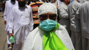 A Muslim pilgrim wears a surgical mask to help prevent infection from a respiratory virus known as the Middle East Respiratory Syndrome (MERS) in the holy city of Mecca, Saudi Arabia, on May, 13, 2014. (AP Photo/Hasan Jamali)