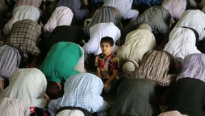 An Iranian boy stands among Shi'ite Muslim worshippers attending the weekly Friday prayer on May 16, 2014, at the university of the Iranian capital, Tehran. (AFP PHOTO/ATTA KENARE)