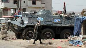 A soldier walks near an armoured military vehicle at a checkpoint to the capital city, Sana'a, on May 3, 2014. (REUTERS/ Mohamed al-Sayaghi)