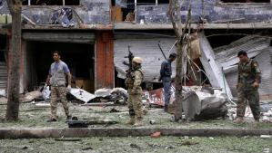 Afghan security personnel investigate the site of a suicide attack that struck the convoy of presidential candidate Abdullah Abdullah in Kabul, Afghanistan, on Friday, June 6, 2014. (AP Photo/Rahmat Gul)