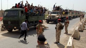 Iraqi men who volunteered to join the fight against a major offensive by jihadists in northern Iraq stand on army trucks as they leave a recruiting center in Baghdad on June 13, 2014. (AFP PHOTO/ALI AL-SAADI)
