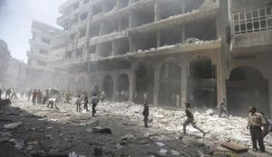 Residents run in a damaged site due to what activists claim was shelling by forces loyal to Syrian President Bashar Al-Assad at a market in central Duma, in Eastern Ghouta, on June 15, 2014. (REUTERS/Bassam Khabieh)