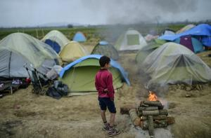 A boy stands next to a fire at a makeshift camp set by refugees and migrants stranded by the Balkan border blockade, on April 3, 2016 near the village of Idomeni at the Greek Macedonian border