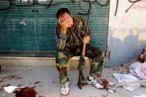 Anti-government fighter hides his face after his friend was shot by a Syrian army sniper. /Reuters