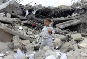 A boy walks as he collects toys from the rubble of a house destroyed by a recent air strike in Yemen's northwestern city of Saada