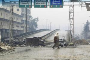 A man crosses the Al-Haj highway, which is closed because of sniper fire by forces loyal to Syria's President Bashar Al-Assad, in Aleppo