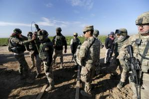 U.S.-led coalition instructors monitor as they train Iraqi soldiers from the army's 72nd infantry brigade while participating in a joint live ammunition exercise at Besmaya military base in south of Baghdad