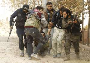 Free Syrian Army fighters carry a wounded comrade during clashes with Assad's forces, near a crucial strategic stronghold outside Aleppo.