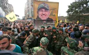 Hezbollah members carry a picture of top Hezbollah commander Mustafa Badreddine during his funeral in Beirut's southern suburbs