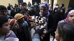 Residents queue to receive new and second-hand clothes as part of humanitarian aid at a school in Aleppo. File photo.