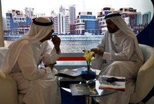 File photo - Businessmen speak to each other during the Cityscape real estate exhibition in Dubai October 2, 2012. REUTERS/Ahmed Jadallah