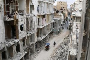 Residents walk near damaged buildings in the rebel held area of Old Aleppo. REUTERS/Abdalrhman Ismail