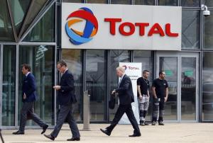 People walk past the entrance of French oil giant Total headquarters in the financial and business district of la Defense near Paris