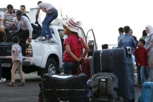 A Syrian girl waits near suitcases as other Syrians arrive at Lebanon's northern Tripoli port to embark a passenger ferry to Turkey September 22, 2015. REUTERS/Jamal Saidi