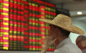 An investor looks at an electric board shwoign stock information at a brockerage house in Haikou. Hainan province, China, August 11, 2015. Reuters/Stringer
