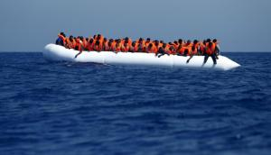 Migrants on a rubber dinghy wait to be rescued by the Migrant Offshore Aid Station (MOAS) ship MV Phoenix, some 20 miles (32 kilometers) off the coast of Libya, August 3, 2015. Some 118 migrants were rescued from a rubber dinghy off Libya on Monday morning. The Phoenix, manned by personnel from international non-governmental organizations Medecins san Frontiere (MSF) and MOAS, is the first privately funded vessel to operate in the Mediterranean. REUTERS/Darrin Zammit Lupi