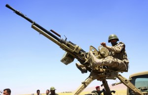A member of the Kurdish peshmerga forces sit with a weapon during an intensive security deployment.